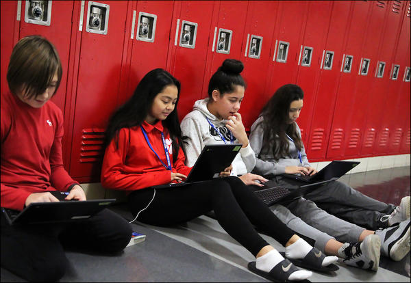 Elm students use Chromebooks while seated in the second-floor hallway.