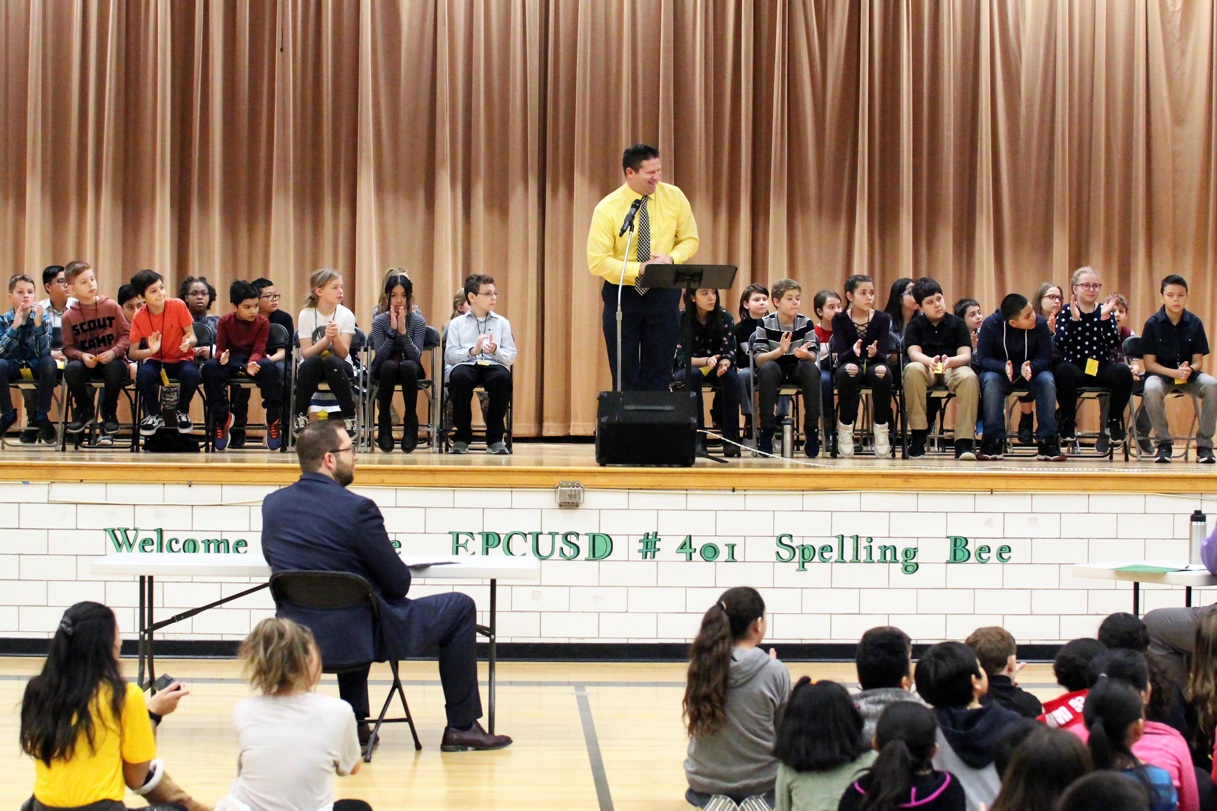 Elmwood Principal Mr. Matthew Lerner welcomes students, parents and guests to the 2019 District 401 Spelling Bee. Superintendent of Schools Dr. Nicolas Wade, the event's official pronouncer, is seated to the left. District 401 photo by Dave Porreca (click image for larger view).
