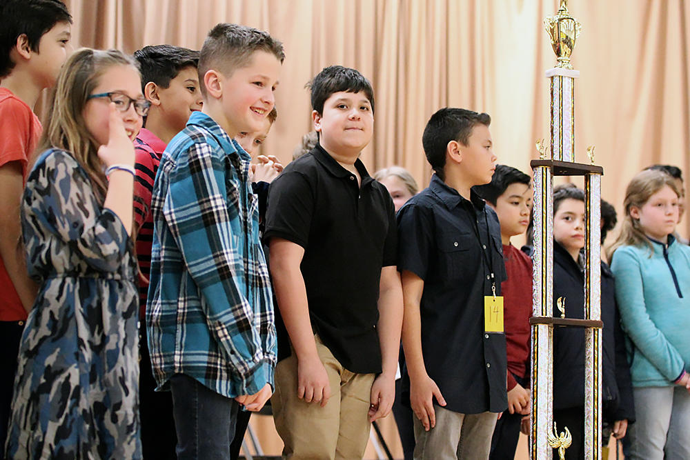 Spelling Bee competitors from Elmwood and John Mills surround the victory trophy after Elmwood 6th graders Nico Di Naso and Steve Rodriguez won first and second place, respectively.