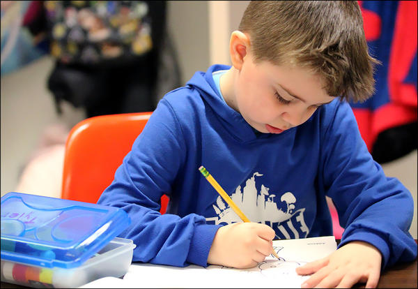 A kindergarten student works at his desk.