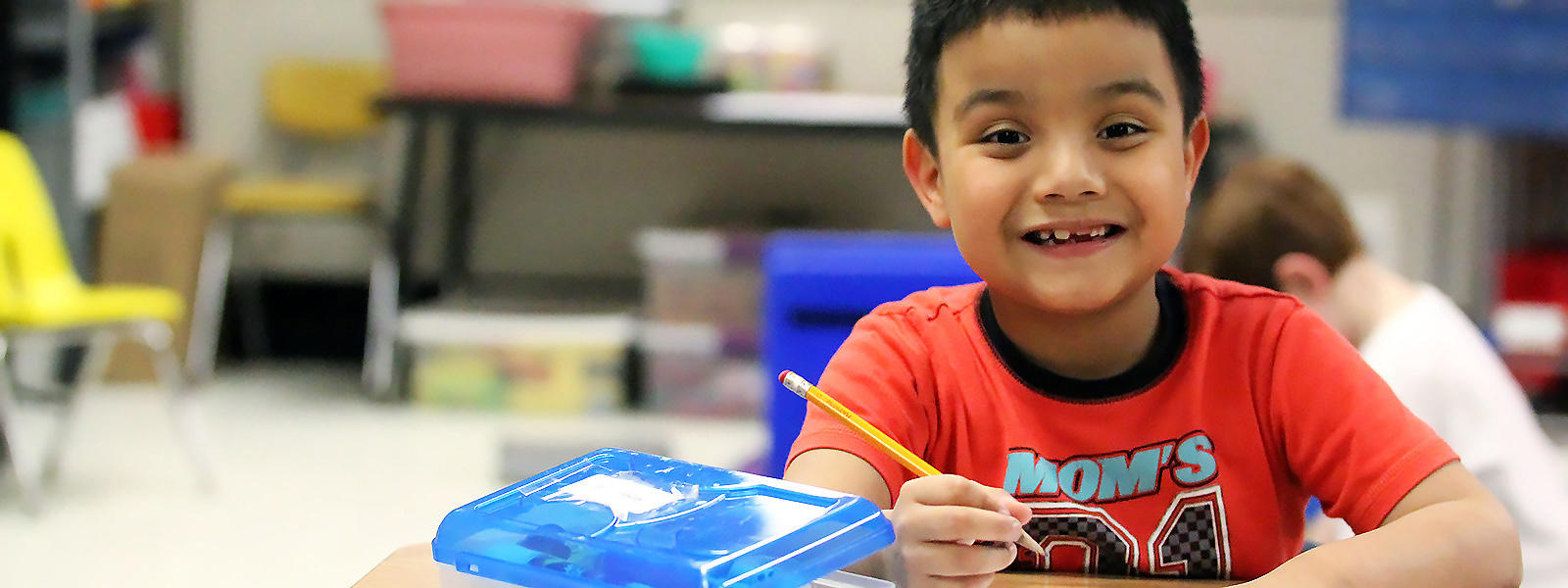A student in Ms. Barbara Bocka's afternoon kindergarten class smiles at the camera while working on an assignment at his desk.