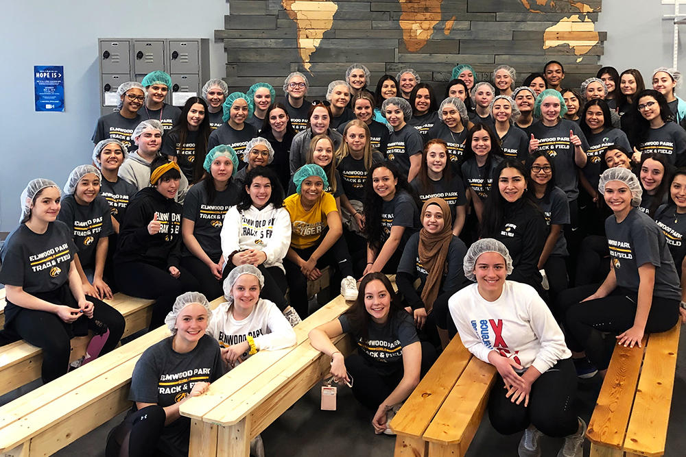 The girls track & field team gathers for a group photo at Feed My Starving Children in Schaumburg.