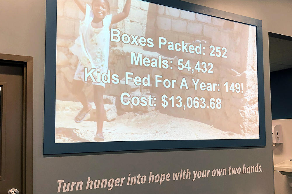 Numbers on a screen show how many children the girls track & field team will feed thanks to their efforts at Feed My Starving Children.