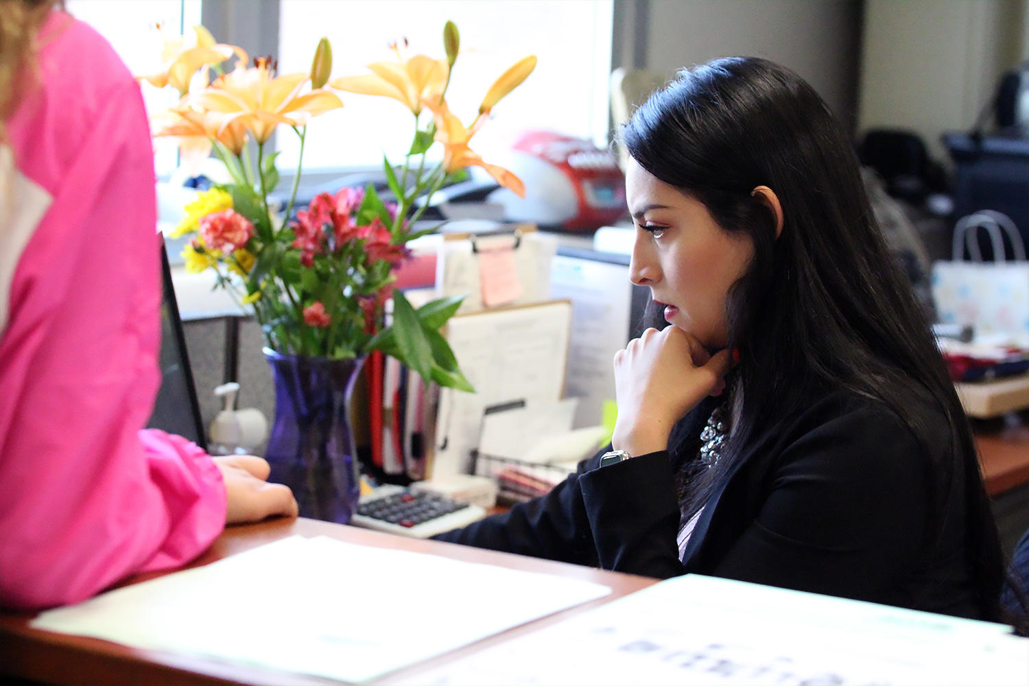 Jessica Solis helps a student in the Elmwood main office.