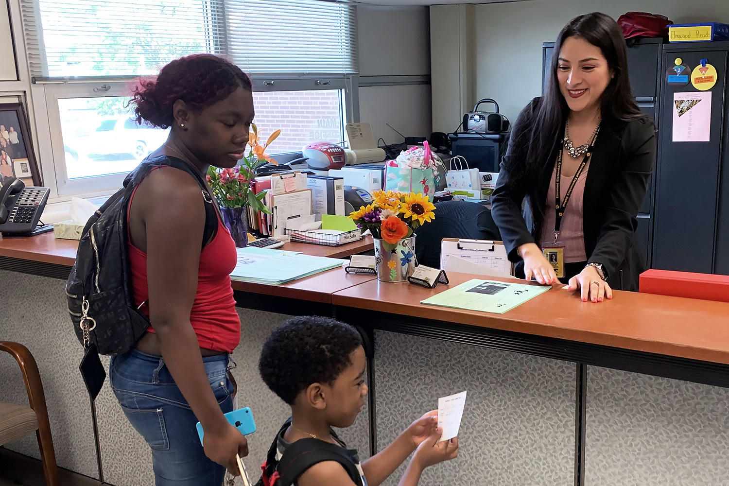 Jessica Solis helps an Elmwood parent and student.