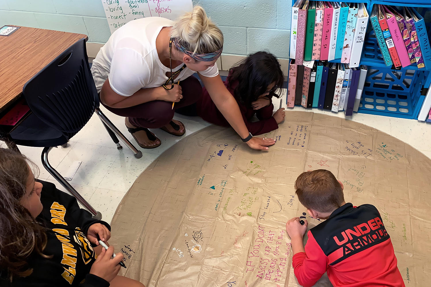 Lauren Jerzyk helps her students as they write positive messages on a circle mat.