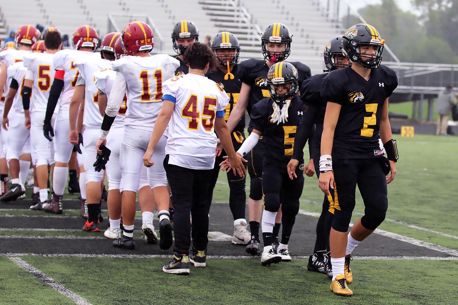EPHS quarterback Mike Stranski (2) leads the Tigers through their postgame handshakes with the Westmont Sentinels.