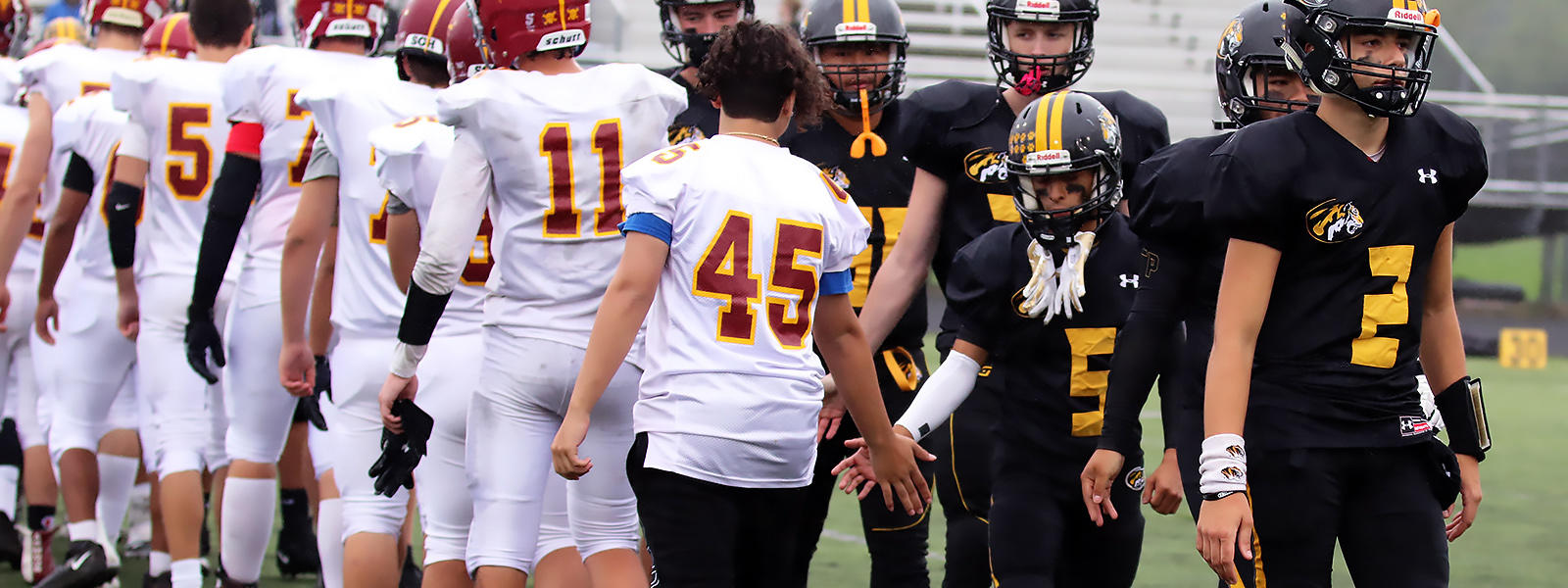 Elmwood Park and Westmont players display good sportsmanship after the Tigers' 13-0 Homecoming victory on Sept. 28.