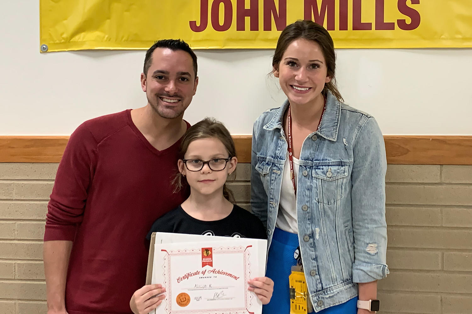 John Mills teachers Collin Sylvano and Nicole Warren congratulate Alicja Rusek on being named one of the top five readers for September in the Chicago Blackhawks' reading program.