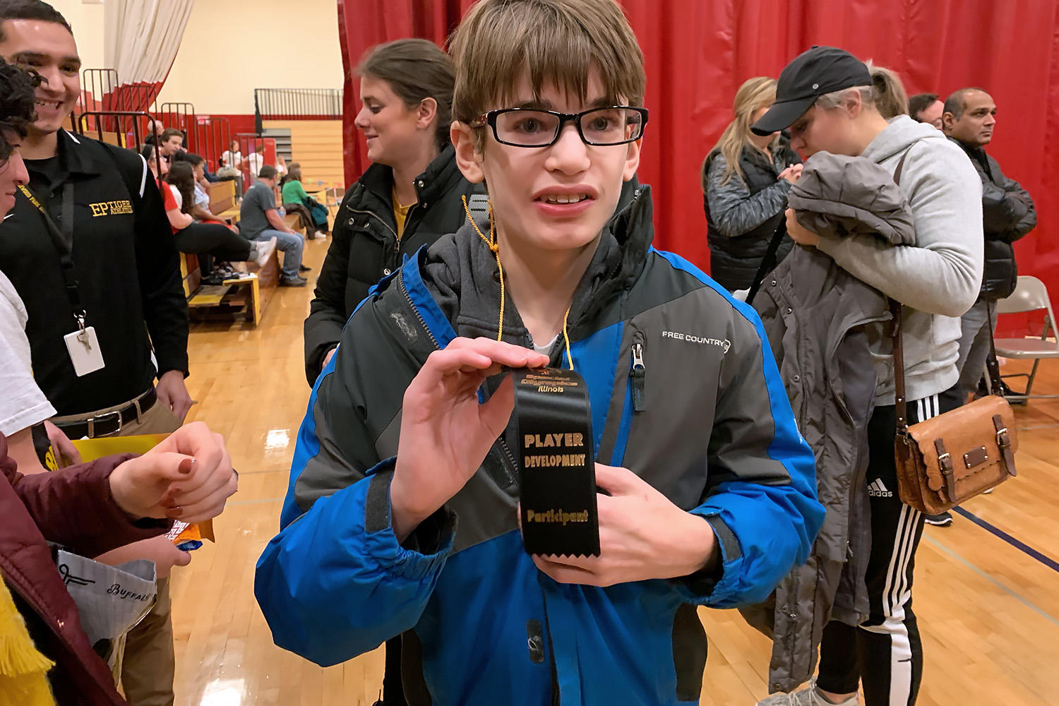 Jonathan from EPHS displays his player development ribbon that he received at the Special Olympics Illinois basketball skills event.