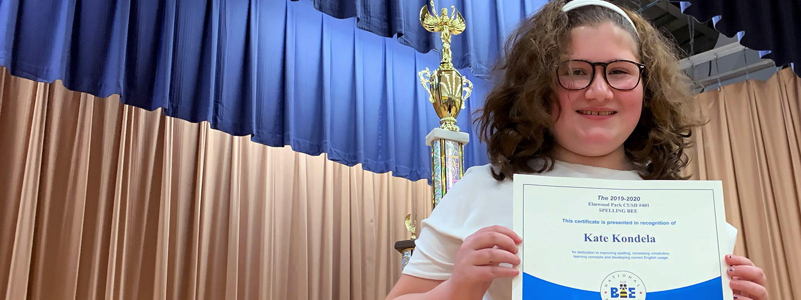 Kate Kondela displays her certificate after winning the 202 District Spelling Bee.