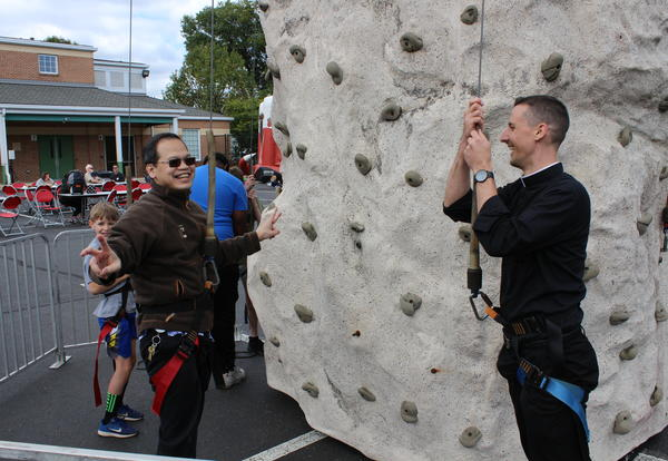 Fr. Vu and Fr. Oetjen Race Up the Wall at the St. James Picnic