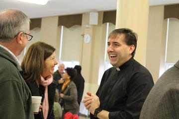 Father Posey speaking and laughing with two parishioners