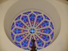 Round Stained Glass Church Window with Wooden Crucifix at the Bottom