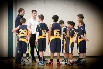 Boys basketball team talking to coaches on the court