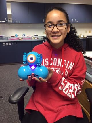 Photo of student in LMC holding small robot