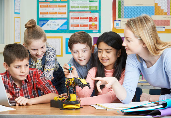 Picture of teacher working with students on a small robot