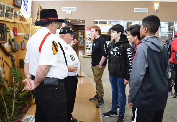 Veteran speaking with three KHS students