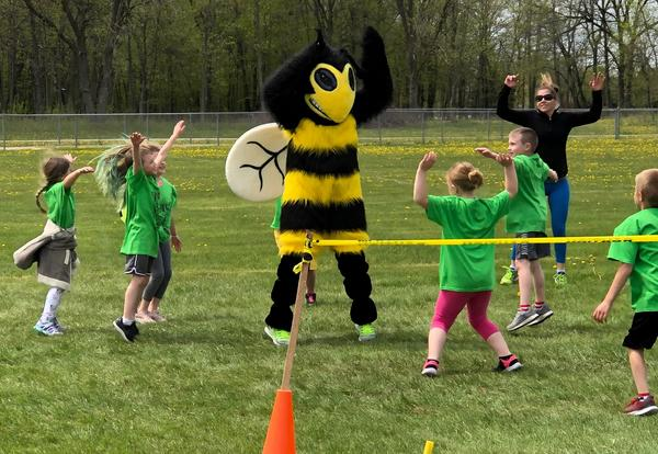 Students warming up with the Stinger mascot