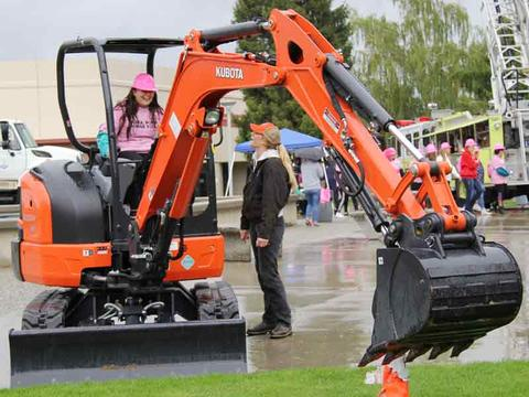 Allie Lerma on an excavator with help from Aerin Sipe of Valley Tractor