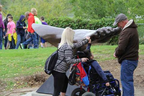 Sculpture Kevin Pettelle with special needs students and his sculpture PED
