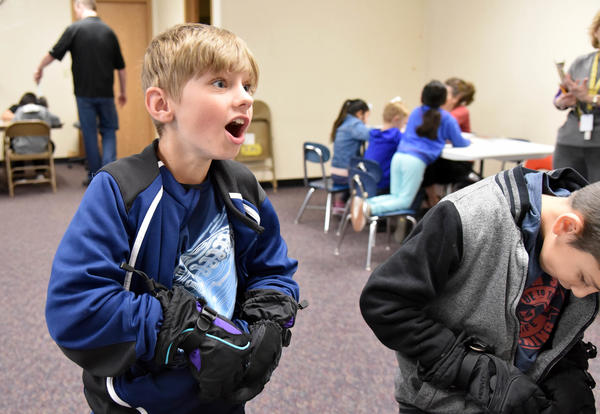 A student tries to zip up his coat while wearing bulky gloves during the IDEA fine motor skills activity