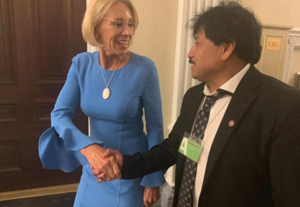 López shakes hands with United States Secretary of Education Betsy DeVos after hearing her speak at the White House.