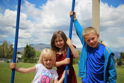Happy children posing for a picture together around a swing