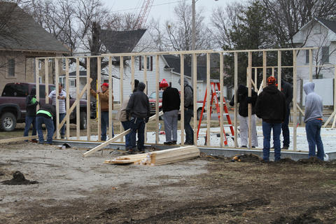Wide angle picture of students working on exterior frame.