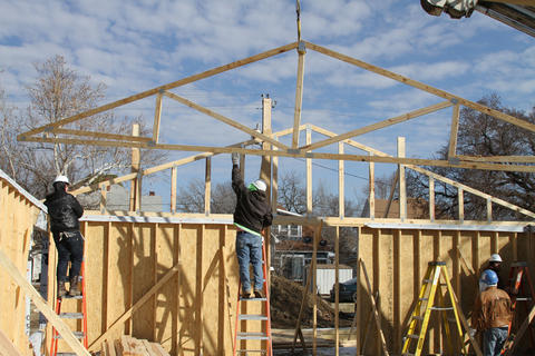 Another view of students connecting trusses to house.