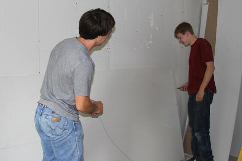 Two students team up to install drywall.