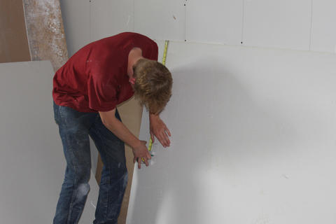 Student making measurement while installing drywall.