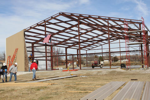 Students starting on metal siding with majority of steel framework still visible.