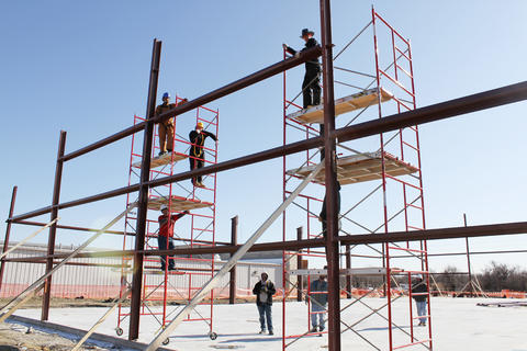 Students on two scaffolds working on framework of building.