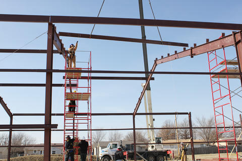 Students on scaffold installing steel roof beam with help from crane.