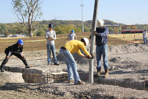 Students pouring concrete reaching location from boom.