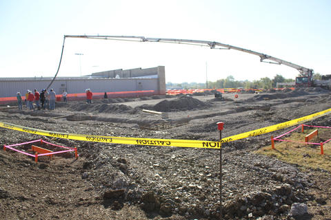 Wide view of construction site with boom from concrete truck reaching across length of foundation.
