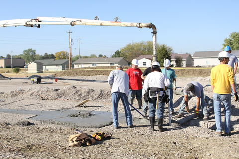 Group of students smoothing out fresh concrete pour for footing.