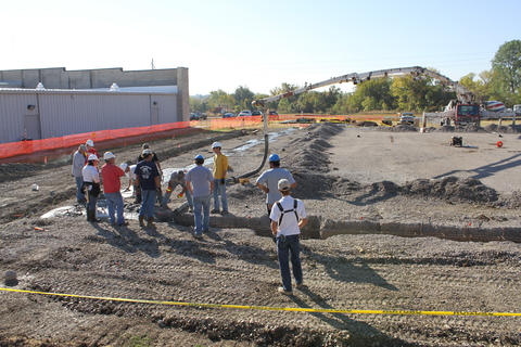 Wide view of students pouring concrete.