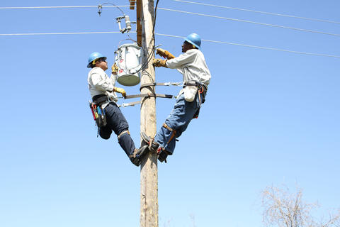 Two students toward top of pole installing transformer.