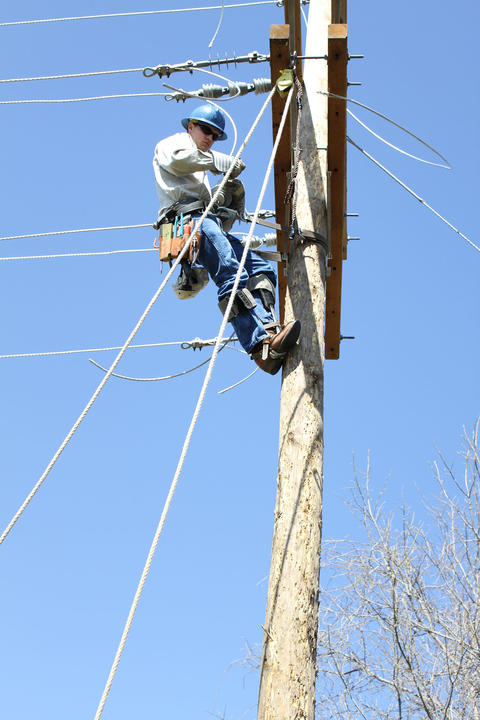 Student on electric pole receiving a transformer via a roping system.