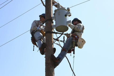 Another picture of two students assisting each other with transformer installation.