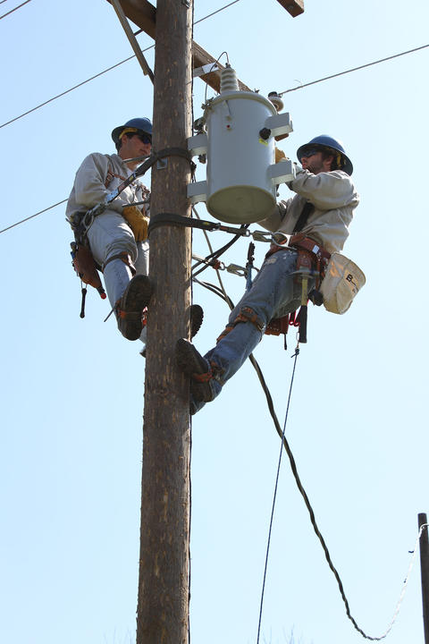 Closer shot of students working installing transformer to top of pole.