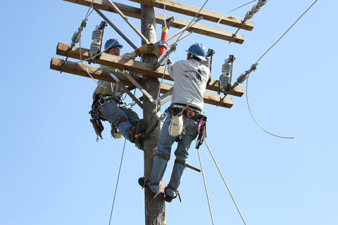 View from behind of a pair of students on top of pole installing a transformer.
