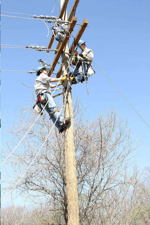 Two students receiving a transformer at top of pole via a rope pulley system.