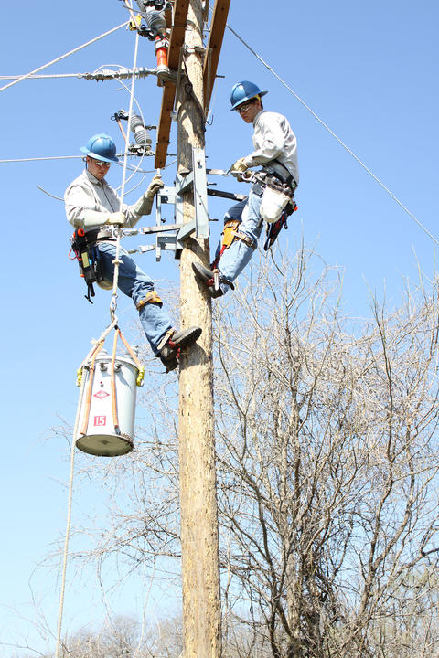 Students at top of pole receiving transformer from other students at ground who are lifting via rope pulley system.