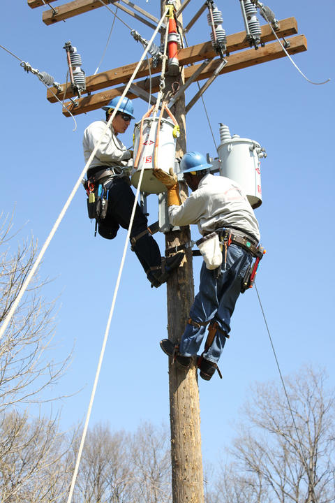 Students installing a second transformer to pole.