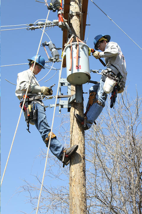 Zoom picture of students installing transformer to top of electric pole.