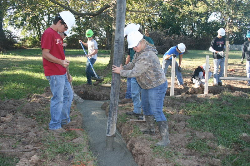 Students Pouring Concrete Into Footings for Foundation