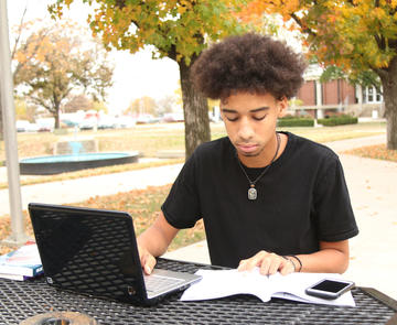 Student Doing Homework on Laptop on Outside Table with Fall Foliage in Background